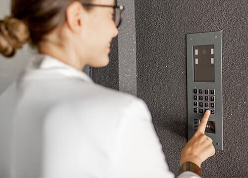woman pressing a button on an apartment intercom system